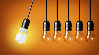 Perpetual motion with light bulbs and energy saver bulb. Idea concept on orange background.
